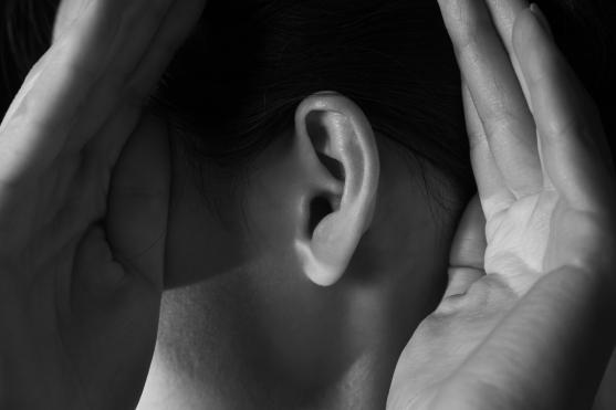 Woman holds her hands near ear